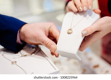 Man buying necklace in jewelry store. Sale and customer service in the store