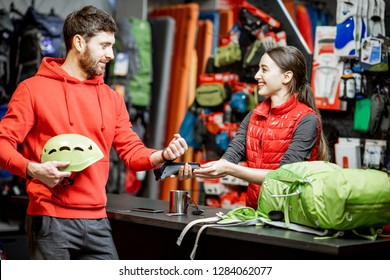 Man buying sports equipment using handwatch at the cash register with saleswoman in the shop with travel goods