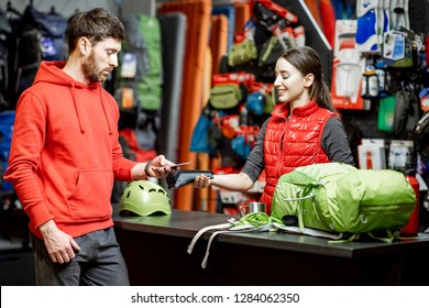 Man buying sports equipment using smart phone at the cash register with saleswoman in the shop with travel goods