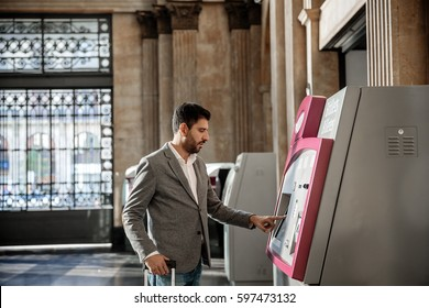 Man buying train tickets at the train station