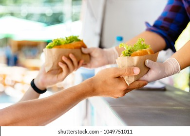 Man buying two hot dog in a kiosk, outdoors. Food concept. Close-up view.