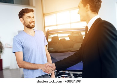 A man buys a new car in a light large car showroom. The seller helps them choose. He is very happy about this, they are in a good mood. There are many modern cars.