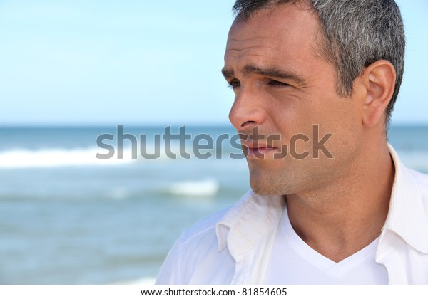Man by the ocean looking into the middle distance
