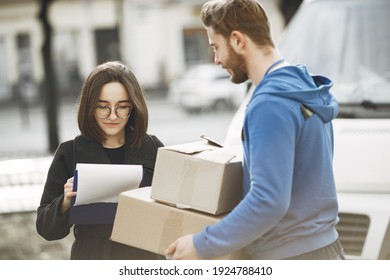 Man by the truck. Guy in a delivery uniform. Delivery man with package outdoors