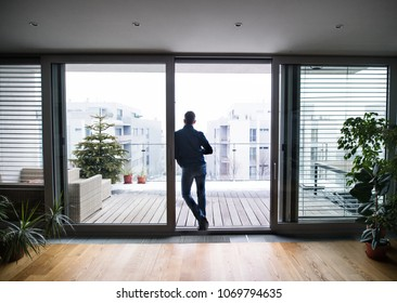 A man by the window holding a cup of coffee at home.