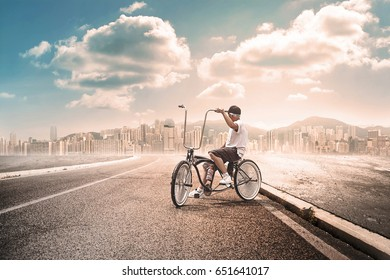 Man with bycicle far from the city