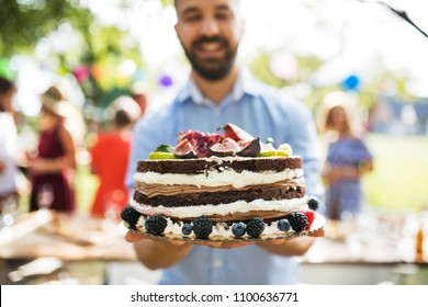 Man with a cake on a family celebration or a garden party outside.