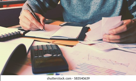 Man calculate about cost and writing make note.