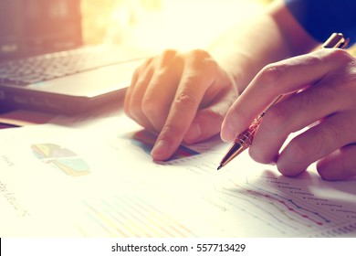 Man calculate cost and expenses and using laptop for search data result