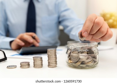 Man calculates the savings. Budget planning concept. Businessman working in the office. Man puts coins into the jar