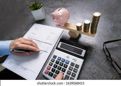 Man Calculating Bill Near Pink Piggybank And Increasing Stacked Coins Balancing On Seesaw