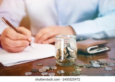 Man calculating home budget, saving money, finance