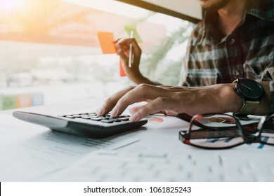 Man calculating individual income tax from financial document during note some data to sticky on window glass with calculator at his office - Business Financial Concept