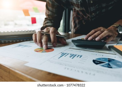 Man calculating individual income tax from financial document with calculator at his office - Business Financial Concept