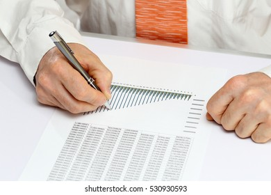 man is calculating on a desk in an office