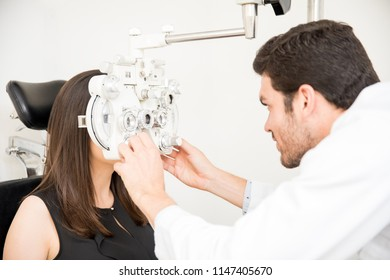 Man calibrating the optical phoropter to exam eyesight of young woman patient