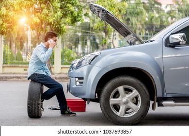 Man call examining a broken car on a sunny day