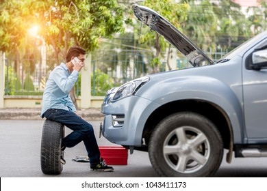 Man call examining a broken car on a sunny day