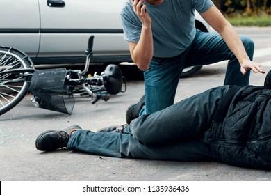 Man calling an ambulance for a victim of a car crash