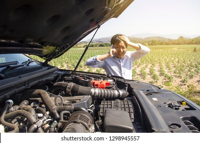 A man is calling a car mechanic because his car is broken.