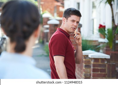 Man Calling For Help On Mobile Phone Whilst Being Stalked On City Street By Woman