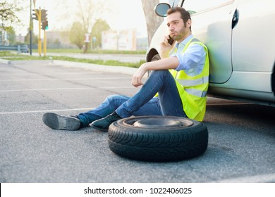 Man calling help service for a flat tyre after vehicle breakdown with smartphone