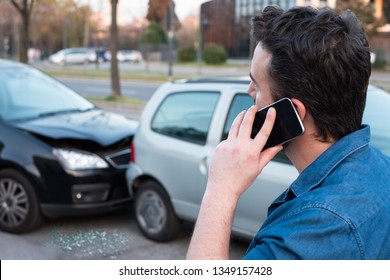 Man calling roadside service after car crash