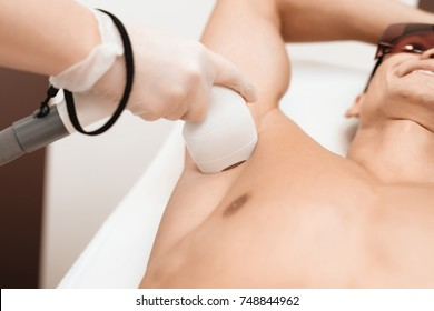 The man came to the procedure of laser hair removal. The doctor treats his armpit with a special apparatus. The man has red glasses.