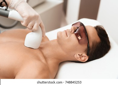 The man came to the procedure of laser hair removal. The doctor treats his neck and face with a special apparatus. The man has red glasses.
