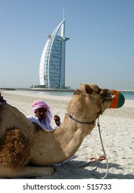 A man and a camel posing in front of the most beautiful hotel in the world in dubai city, UAE