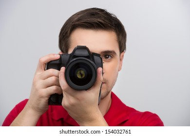 Man with camera. Confident young man holding camera in his hands and focusing at you while isolated on grey