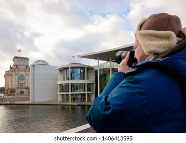 Man with camera at Reichstag building with German Flags in Berlin, capital of Germany in winter in the street. German Bundestag parliament house.