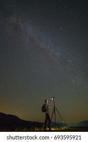 The man with a camera stand on the starry sky background. night time