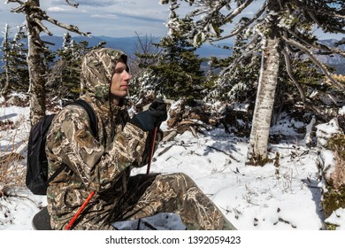 Man in camo clothes and hood, with ski or trekking poles in snow winter forest somewhere on mountains. Maybe soldier or a scout or a hiking tourist