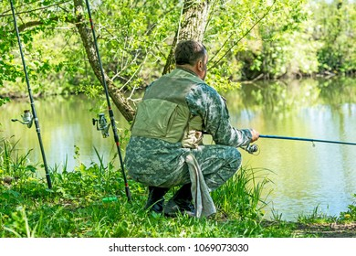 A man in camouflage fishing rod on the river Bank in early summer.