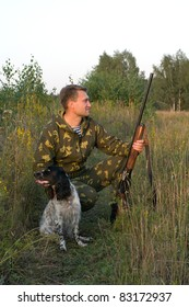 Man in camouflage with a gun and russian hunting spaniel.