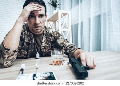 A Man In Camouflage At Home With Shotgun. Depression After War Concept. Sad Homecoming. Returning From Army. Posttraumatic Disorder. Painful Memories. Photo From War. Glass Of Whiskey.