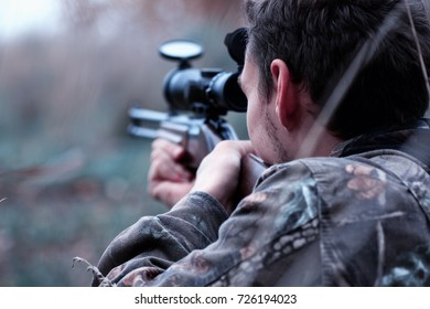 man in camouflage and with a hunting rifle in a forest on a spring hunt