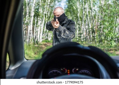 man in camouflage with a pistol aims at the driver of a car on the road in the forest