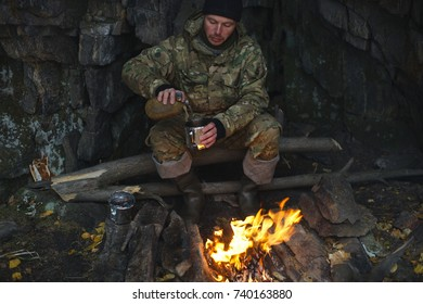 Man in camouflage pours water in a mug to make tea at the stake. Extreme travel. Survival in the wild.