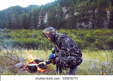 Man in camouflage preparing food on campfire in a clearing near the mountains. the Stalker, survive in the woods