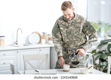 Man in camouflage uniform pouring coffee in cup at kitchen