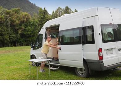 Man with campervan on campground - Coromandel, New Zealand