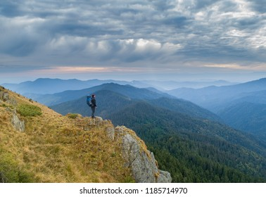 The man with a camping backpack standing on the rock