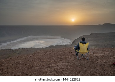 Man in a camping chair at a vulcanic crater during sunrise (Al Wahbah crater in Saudi Arabia)