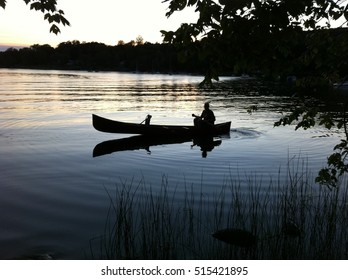 man in a canoe on a lake at dusk
