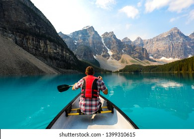 Man canoeing with red life jacket on Moraine Lake in the Canadian Rockies  of Banff National Park, Alberta