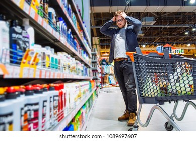 man can't decide in store what to buy. shopping concept. copy space