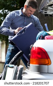 Man can't put luggage into car trunk