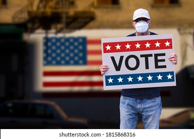 Man with cap blue jeans and medical mask holding a cardboard sign text VOTE with american stars and stripes flag on a wall in the background. American Presidential patriotic background election day.